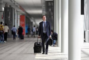 Geschäftsmann auf einer Messe mit einem Koffer
