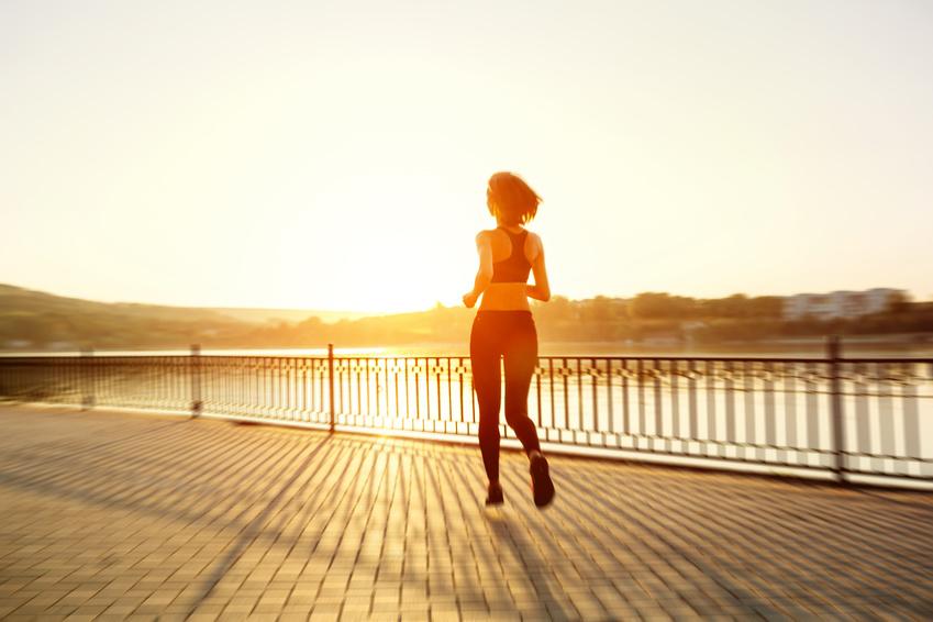 Fitness Frau joggt am Rhein in der Abendsonne